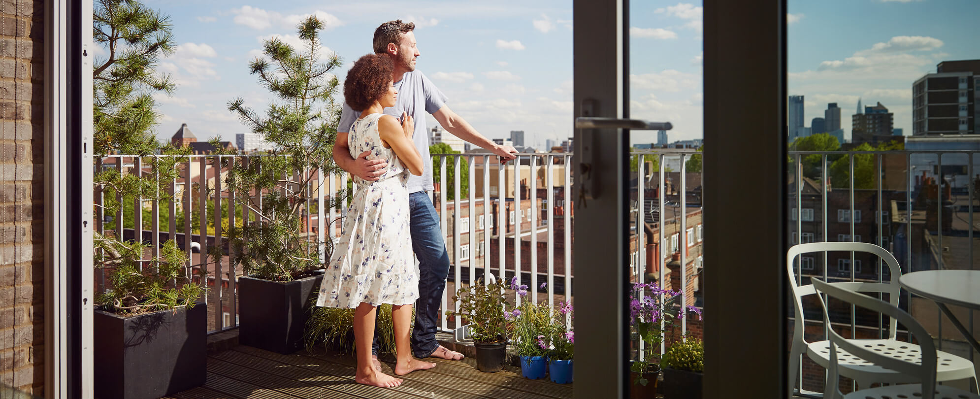Couple on balcony looking out at city