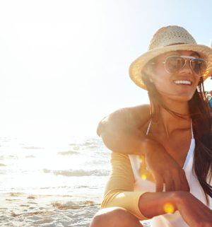 Young couple wearing hats, smiling and sitting on the beach