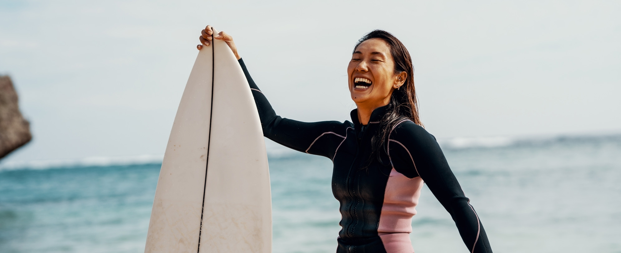 Excited woman in a wetsuit holding surfboard on the beach