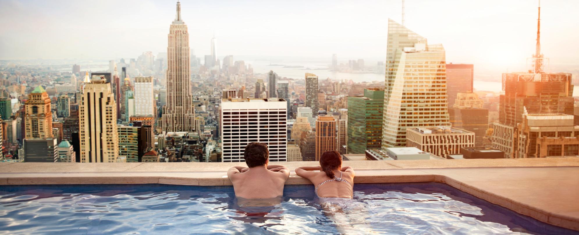 Couple leaning on the edge of an infinity pool overlooking city views