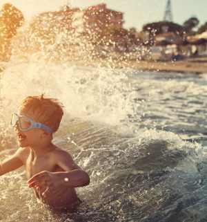 Little boy wearing goggle crashing into an ocean wave