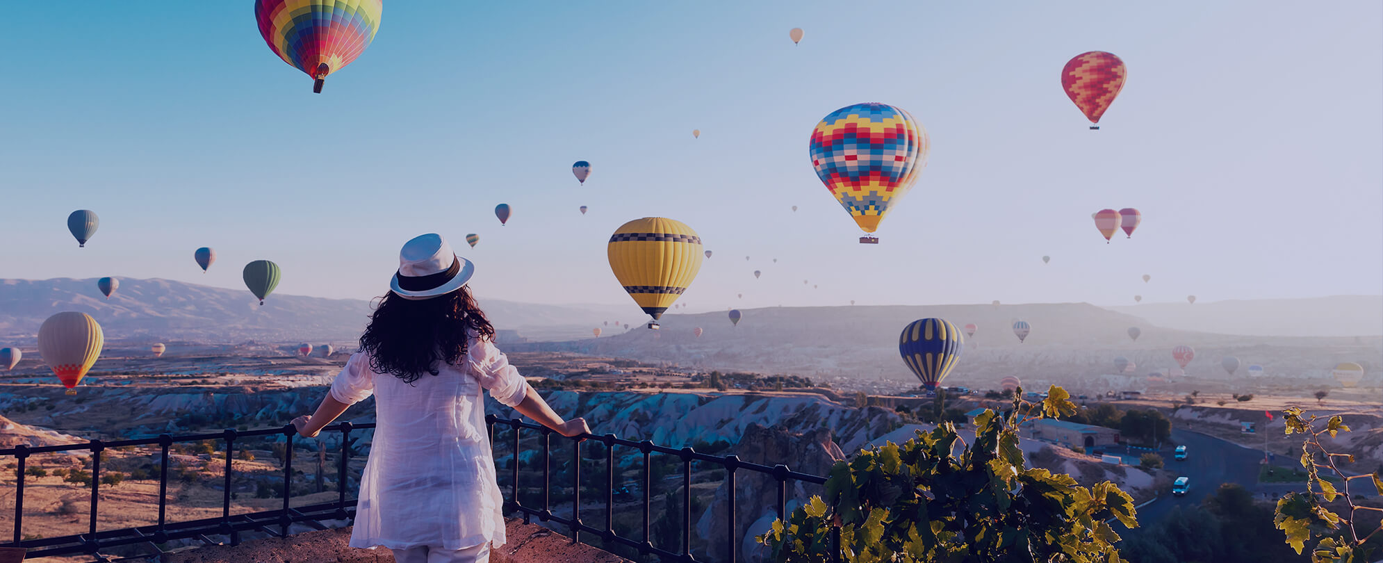 Woman in hat looking at hot airballoons