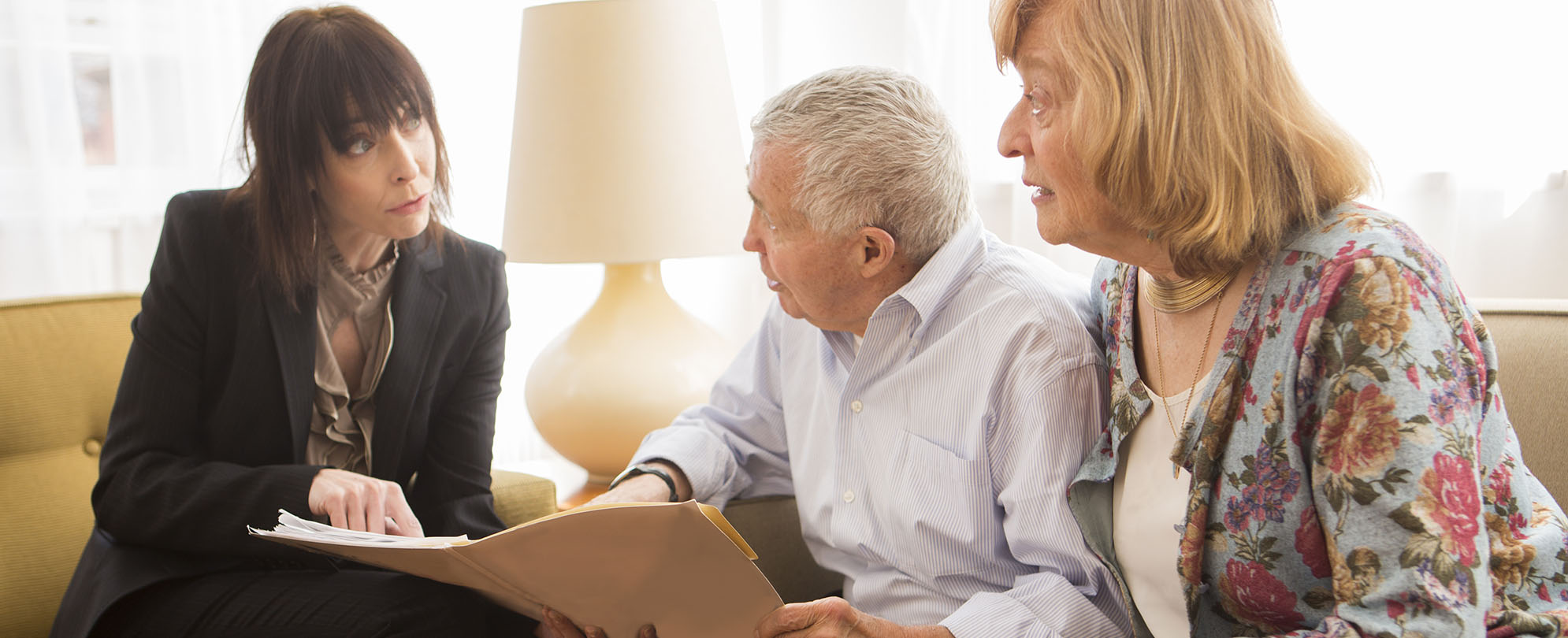 Concerned elderly couple reviewing paperwork with an attorney