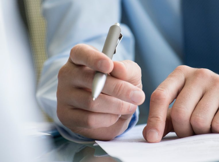 Close up of a timeshare attorneys hand, holding a pen, and reviewing an important timeshare document