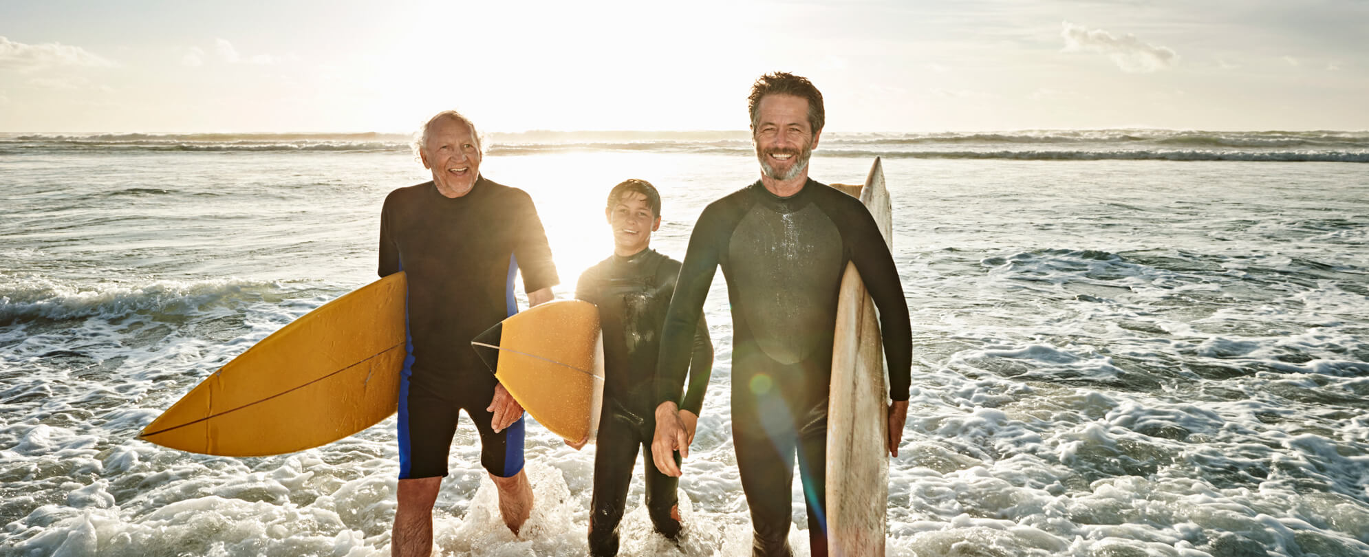 Grandfather, father, and son walking on to the shore with surfboards in hand