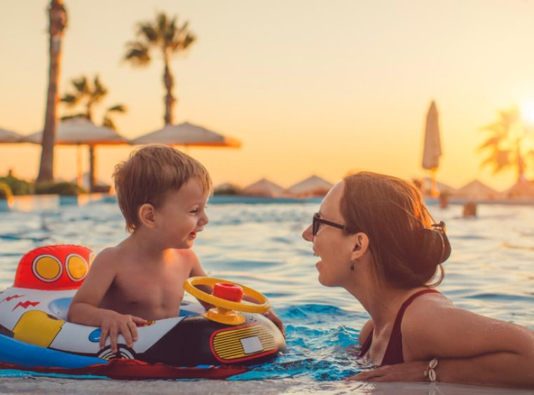 Mother talking to baby son on a pool float