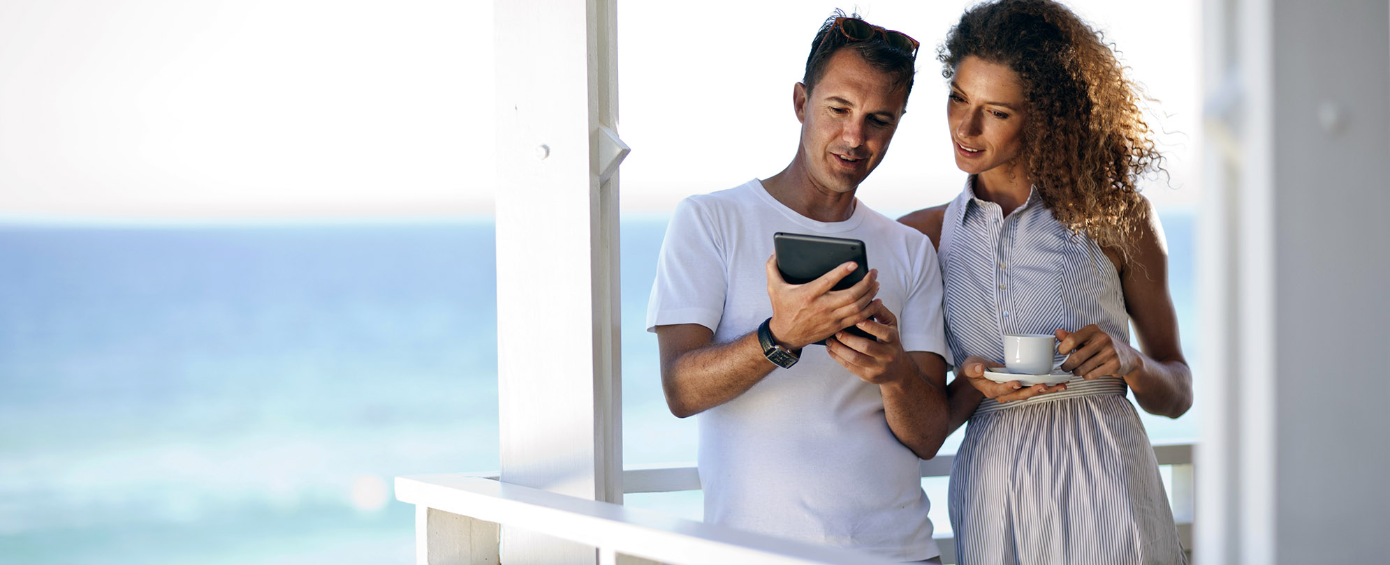Couple having their morning coffee on a balcony overlooking the ocean while reviewing documents on an iPad