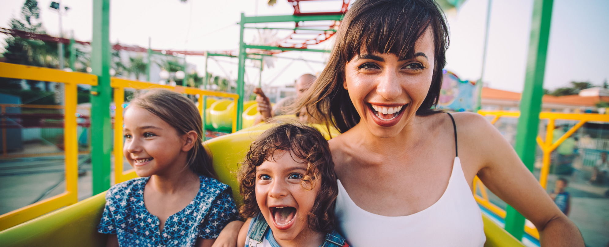 Mother and two daughters laughing on a caterpillar amusement park ride