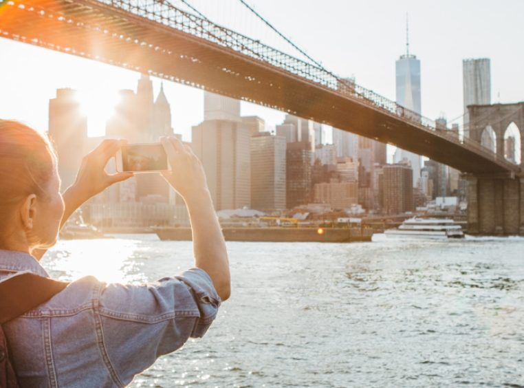 Woman taking a photograph with her phone of the Brooklyn Bridge in New York, NY.