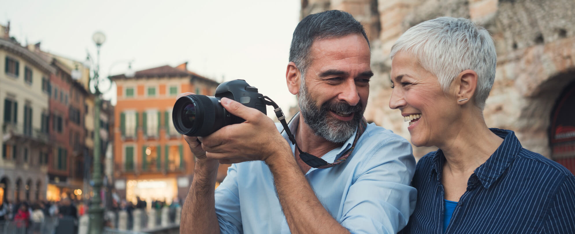 Man smiling in baby blue shirt holding up his DSLR camera